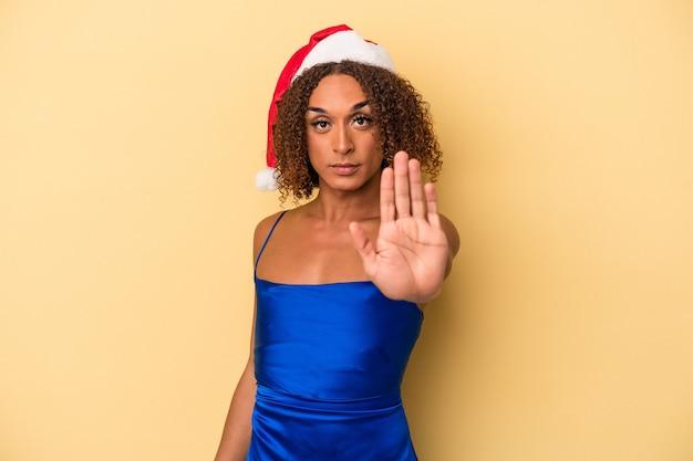 一時停止の標識を示す伸ばした手で立っている黄色の背景に分離されたクリスマスを祝う若いラテントランスセクシュアル女性は、あなたを防ぎます。