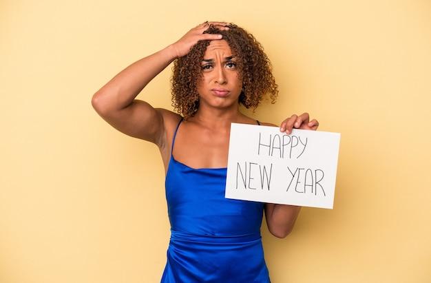 ショックを受けている黄色の背景で隔離された新年を祝う若いラテン系の性転換者の女性、彼女は重要な会議を思い出しました。