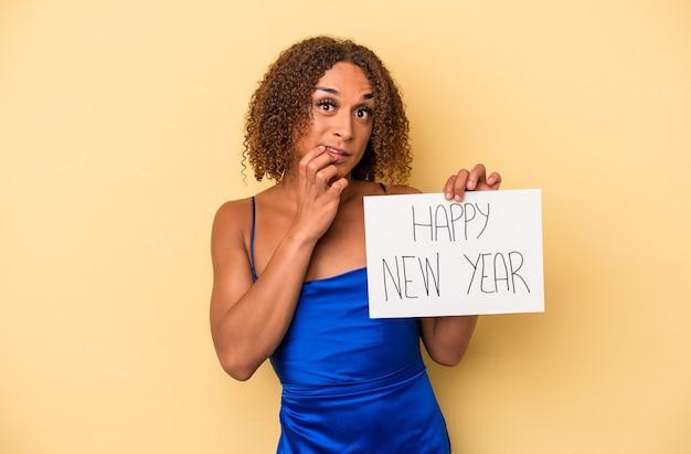 新年を祝う若いラテン系のトランスセクシュアルの女性は、黄色の背景に爪を噛んで、神経質で非常に心配しています。