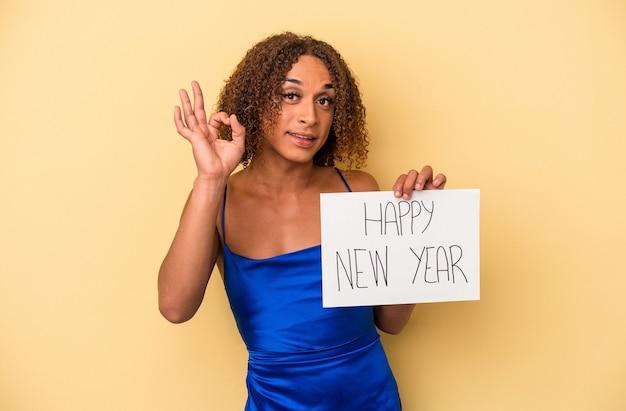 新年を祝う若いラテン系のトランスセクシュアル女性は、黄色の背景に孤立し、陽気で自信を持って大丈夫なジェスチャーを示しています。