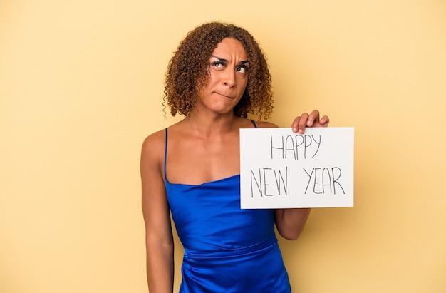 黄色の背景で隔離された新年を祝う若いラテン系の性転換者の女性は混乱し、疑わしく、不安を感じています。