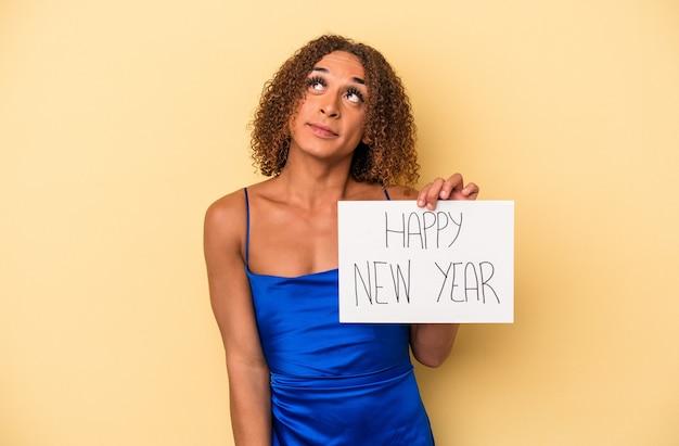目標と目的を達成することを夢見ている黄色の背景に分離された新年を祝う若いラテントランスセクシュアル女性
