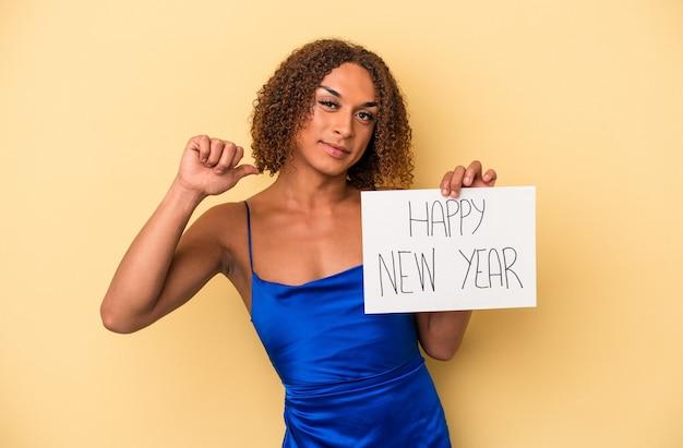 黄色の背景で隔離された新年を祝う若いラテン系の性転換者の女性は、誇りと自信を持って感じています。