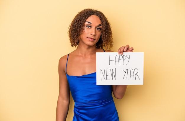 新年を祝う若いラテン系のトランスセクシュアル女性は、幸せ、笑顔、陽気な黄色の背景で隔離。