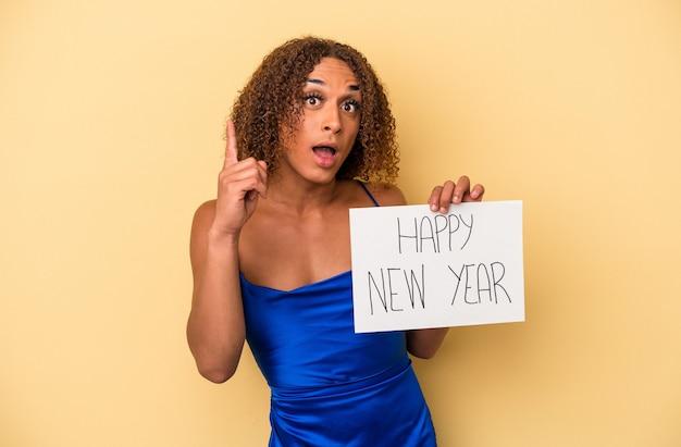 アイデア、インスピレーションの概念を持っている黄色の背景に分離された新年を祝う若いラテントランスセクシュアル女性。