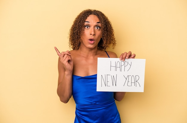 いくつかの素晴らしいアイデア、創造性の概念を持っている黄色の背景に分離された新年を祝う若いラテントランスセクシュアル女性。