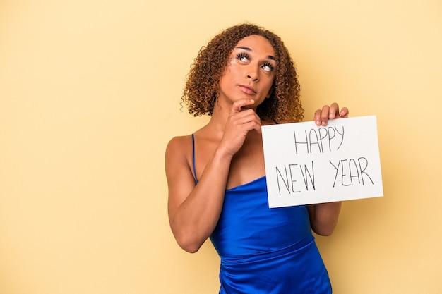 疑わしいと懐疑的な表現で横向きに見える黄色の背景に分離された新年を祝う若いラテントランスセクシュアル女性。