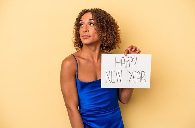 黄色の背景に分離された新年を祝う若いラテン系の性転換者の女性は、笑顔、陽気で楽しい脇に見えます。
