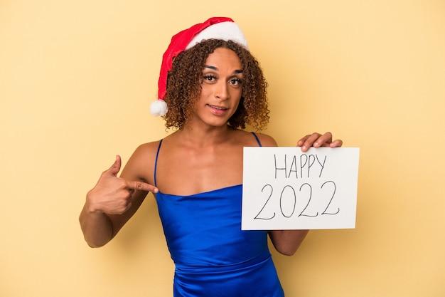 シャツのコピースペースを手で指している黄色の背景の人に孤立した新年を祝う若いラテントランスセクシュアル女性、誇りと自信を持って