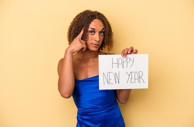 新年を祝う若いラテン系のトランスセクシュアル女性は、指で寺院を指して、黄色の背景で隔離され、タスクに焦点を当てて考えています。