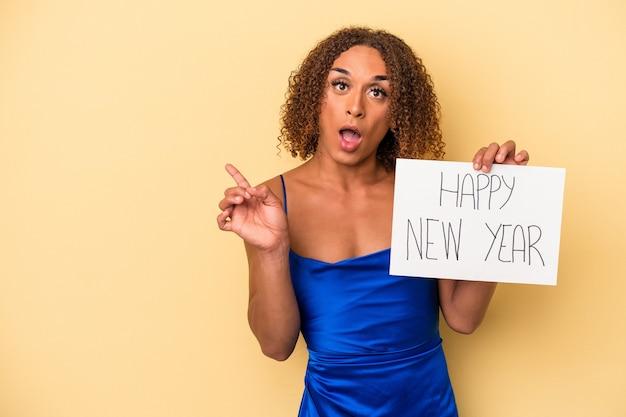 側を指している黄色の背景に分離された新年を祝う若いラテントランスセクシュアル女性