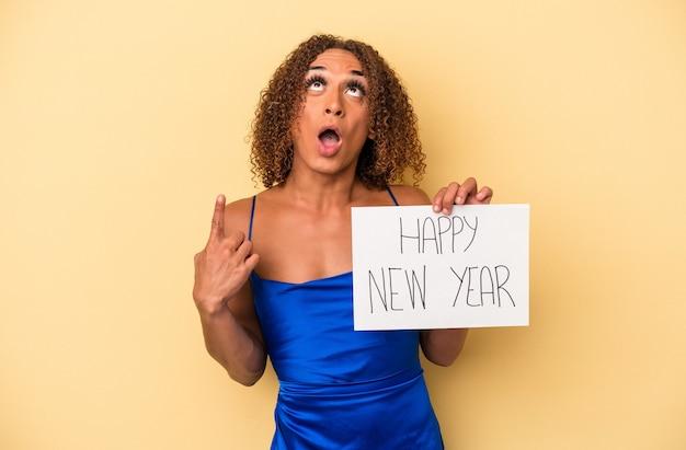 開いた口で逆さまを指している黄色の背景に分離された新年を祝う若いラテン系トランスセクシュアル女性。