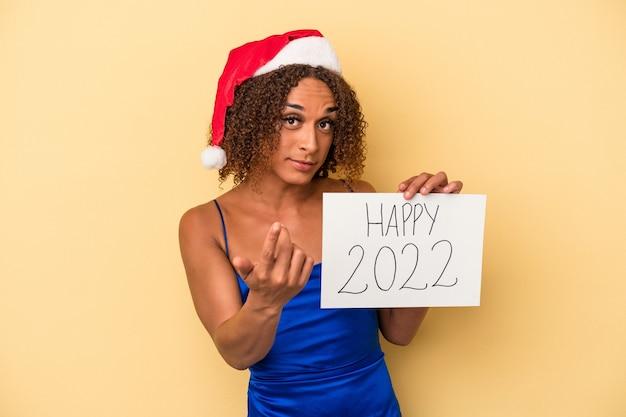 新年を祝う若いラテン系のトランスセクシュアル女性は、招待が近づくようにあなたに指を指して黄色の背景に分離されました。