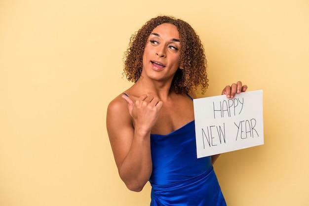 新年を祝う若いラテン系のトランスセクシュアル女性は、親指の指を離れて、笑ってのんきな黄色の背景のポイントで隔離されます。