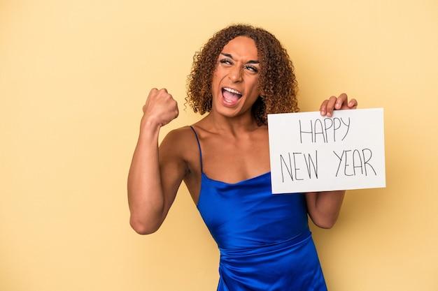 勝利、勝者の概念の後に拳を上げる黄色の背景に分離された新年を祝う若いラテントランスセクシュアル女性。