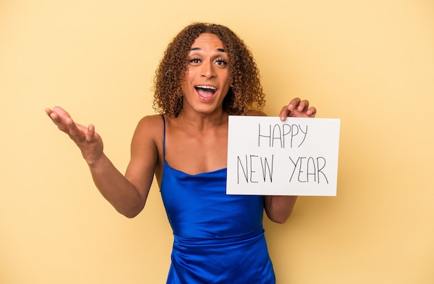 黄色の背景で隔離された新年を祝う若いラテン系のトランスセクシュアル女性は、嬉しい驚きを受け取り、興奮し、手を上げます。