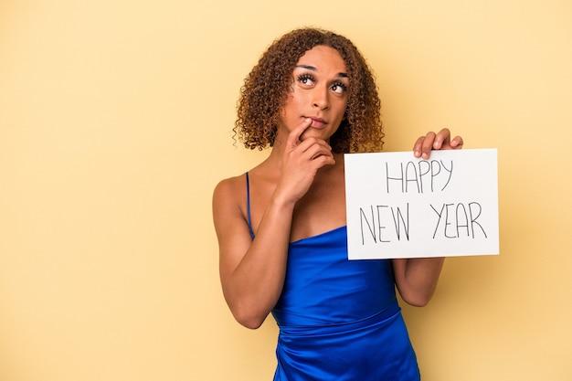 黄色の背景で隔離された新年を祝う若いラテン系の性転換者の女性は、コピースペースを見ている何かについて考えてリラックスしました。