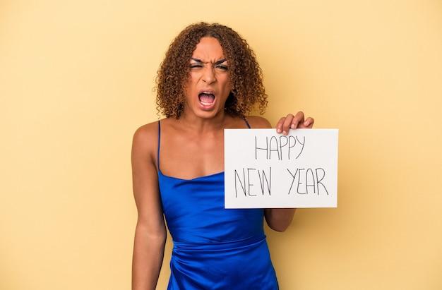 非常に怒って攻撃的な叫び声黄色の背景に分離された新年を祝う若いラテントランスセクシュアル女性。