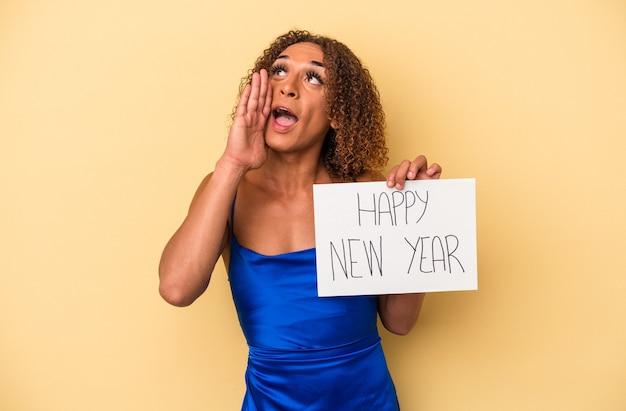 新年を祝う若いラテン系のトランスセクシュアル女性は、開いた口の近くで叫び、手のひらを保持している黄色の背景に分離されました。