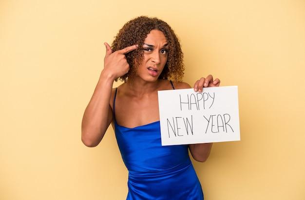 人差し指で失望のジェスチャーを示す黄色の背景に分離された新年を祝う若いラテントランスセクシュアル女性。