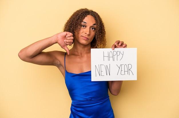 嫌いなジェスチャーを示す黄色の背景に分離された新年を祝う若いラテン系の性転換者の女性は、親指を下に向けます。不一致の概念。