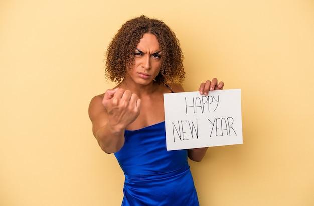 カメラに拳、積極的な表情を示す黄色の背景に分離された新年を祝う若いラテントランスセクシュアル女性。
