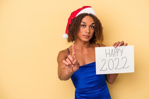 指でナンバーワンを示す黄色の背景に分離された新年を祝う若いラテントランスセクシュアル女性。