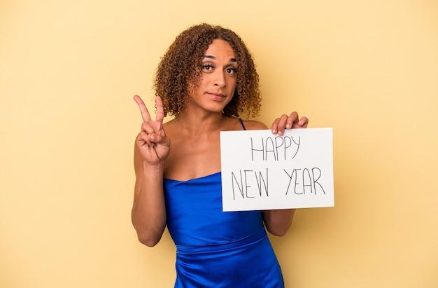 指で2番目を示す黄色の背景に分離された新年を祝う若いラテントランスセクシュアル女性。