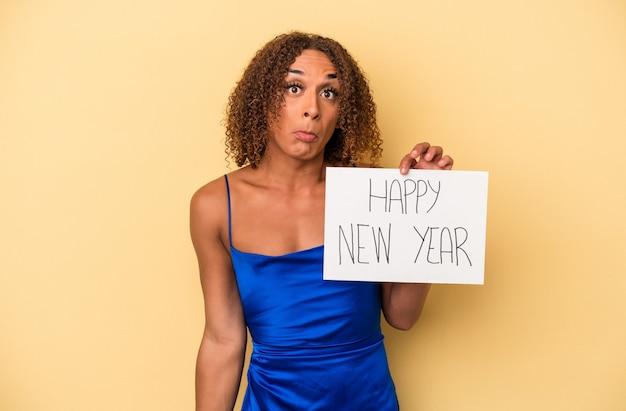 黄色の背景で隔離された新年を祝う若いラテン系の性転換者の女性は肩をすくめると混乱した目を開きます。