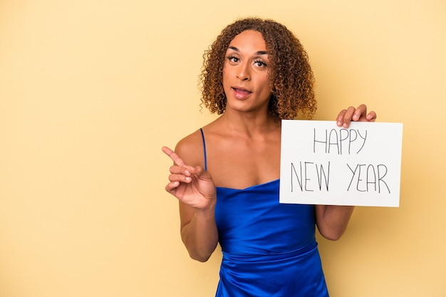 新年を祝う若いラテン系のトランスセクシュアル女性は、笑顔で脇を指して、空白のスペースで何かを示して、黄色の背景に分離されました。