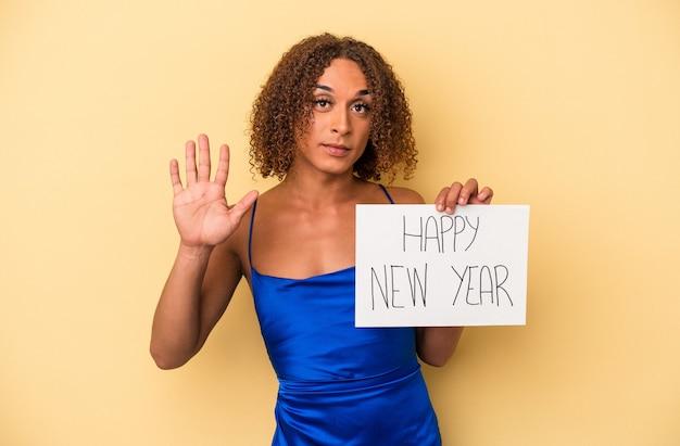 黄色の背景に分離された新年を祝う若いラテン系のトランスセクシュアル女性は、指で5番を示す陽気な笑顔を浮かべています。