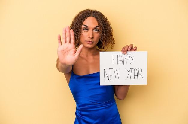 黄色の背景に孤立した新年を祝う若いラテン系のトランスセクシュアル女性は、一時停止の標識を示す伸ばした手で立って、あなたを防ぎます。