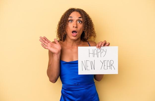 黄色の背景に分離された新年を祝う若いラテン系のトランスセクシュアル女性は驚いてショックを受けました。
