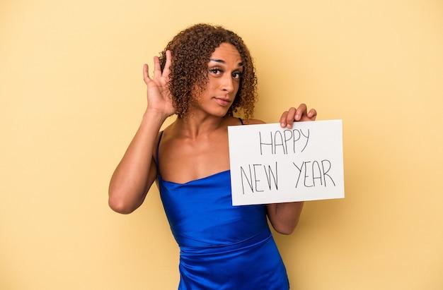 ゴシップを聴こうとしている黄色の背景に分離された新年を祝う若いラテントランスセクシュアル女性。