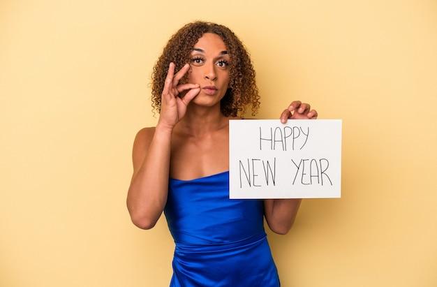 秘密を保持している唇に指で黄色の背景に分離された新年を祝う若いラテン系トランスセクシュアル女性。