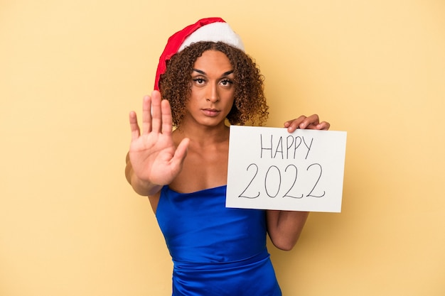 Young latin transsexual woman celebrating new year isolated on yellow background standing with outstretched hand showing stop sign, preventing you.