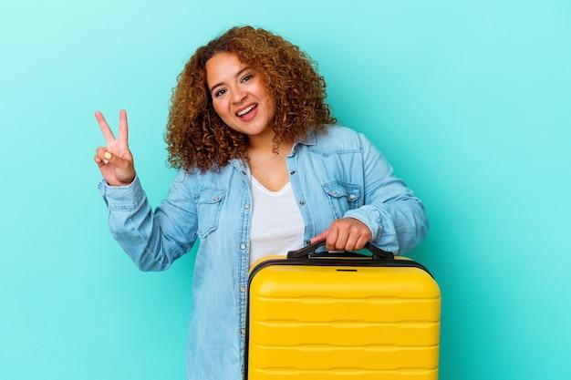 若いラテン旅行者の曲線美の女性は、青の背景にスーツケースを持ち、うれしくて屈託のない、指で平和のシンボルを示しています。