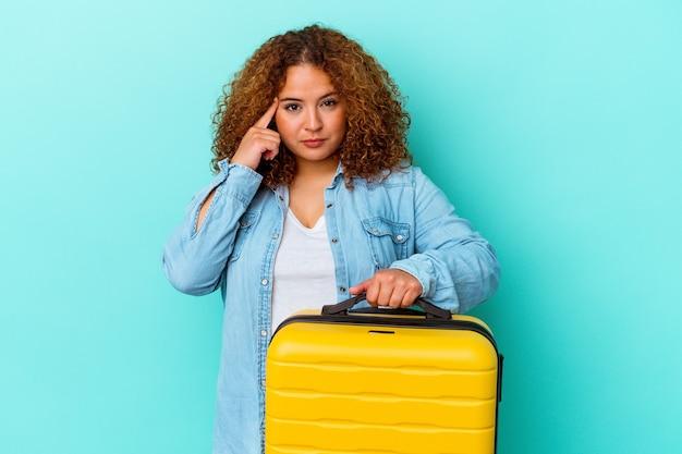 Молодой латинский путешественник пышные женщины держит чемодан, изолированные на синем фоне, указывая храм пальцем, думая, сосредоточился на задаче.