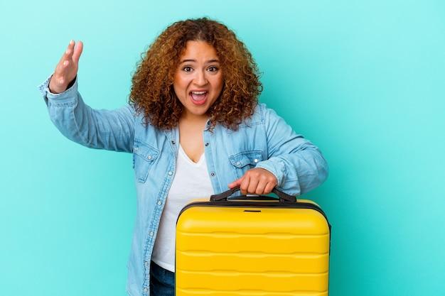 青の背景にスーツケースを持った若いラテン旅行者の曲線美の女性が、うれしい驚きを受け取り、興奮し、手を上げている。