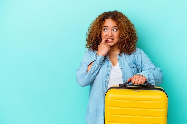 青の背景にスーツケースを持った若いラテン旅行者の曲線美の女性は、コピー スペースを見て何かを考えてリラックスしました。
