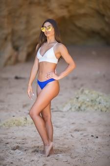 Giovane donna latina in bikini che cammina vicino alle rocce che guarda al mare durante le vacanze estive