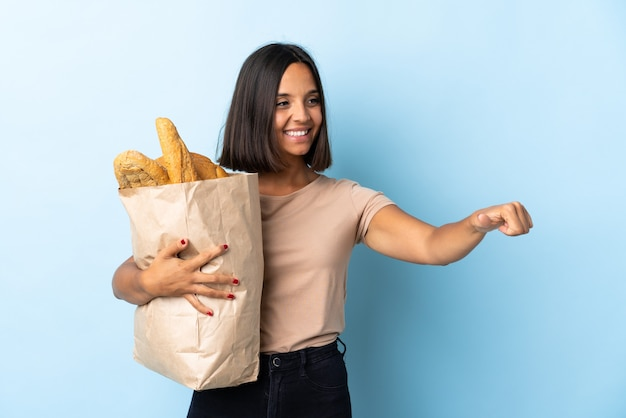 Young latin woman buying some breads isolated on blue background giving a thumbs up gesture