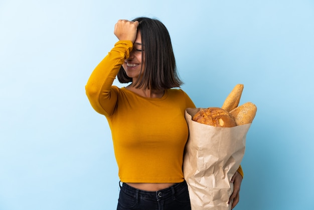 파란색에 고립 된 일부 빵을 사는 젊은 라틴 여자는 뭔가를 깨달았고 해결책을 의도했습니다.