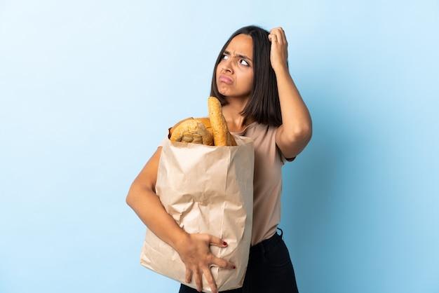 Молодая латинская женщина покупая некоторые хлебы изолированные на сини имея сомнения пока царапающ голову