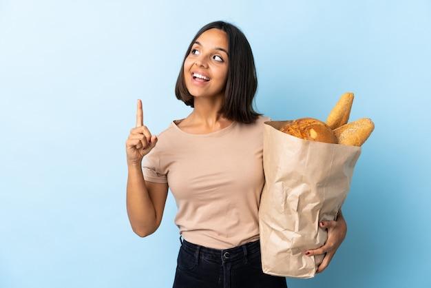 Молодая латинская женщина покупая некоторые изолированные хлебы на сини намереваясь реализовать решение пока поднимающ палец вверх