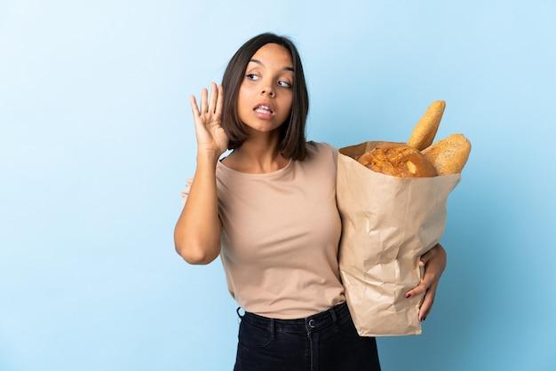 Молодая латинская женщина покупая некоторые изолированные хлеба на сини слушая что-то кладя руку на ухо