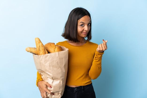 Молодая латинская женщина покупая некоторые изолированные хлеба на сини делая жест денег