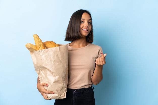 お金のジェスチャーを作る青に分離されたいくつかのパンを購入する若いラテン女性