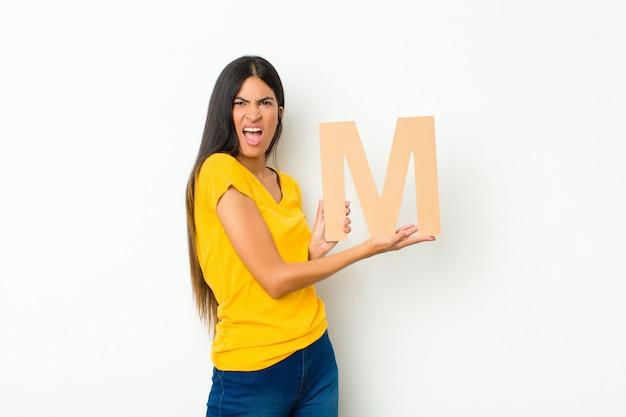 Молодая латинская женщина смущена, сомневается, думает, держа букву m алфавита, чтобы сформировать слово или предложение.