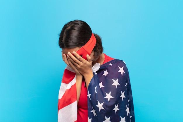 絶望、泣き、側面図の悲しい、欲求不満の表情で手で目を覆っている若いラテン女性